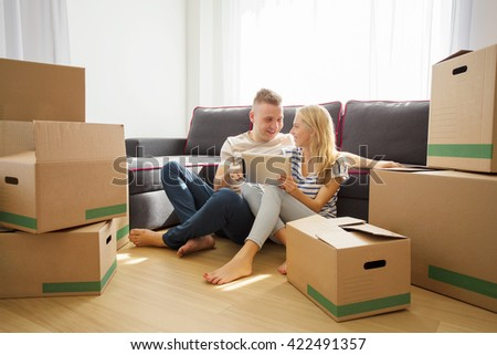 Couple using tablet in their new apartment - stock photo
