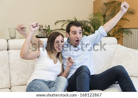couple waching sport on tv and exulting - stock photo