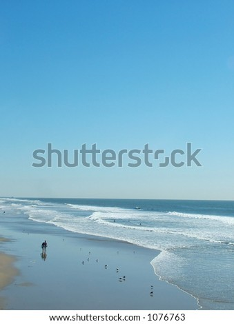 Couple walking along beach - stock photo