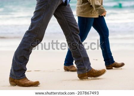 Couple Walking Away on the Beach - stock photo