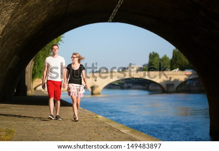 Couple walking by the Seine - stock photo