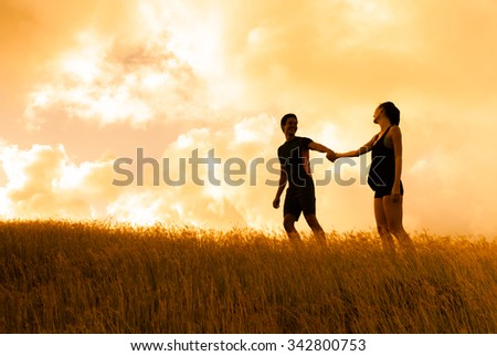 Couple walking in a field holding hands. - stock photo