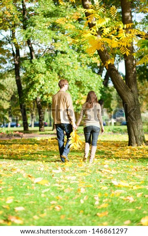 Couple walking in park on a fall day - stock photo