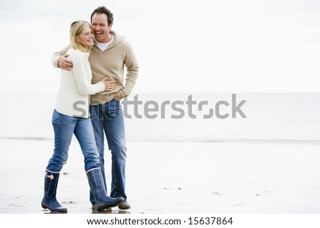 Couple walking on beach arm in arm smiling - stock photo