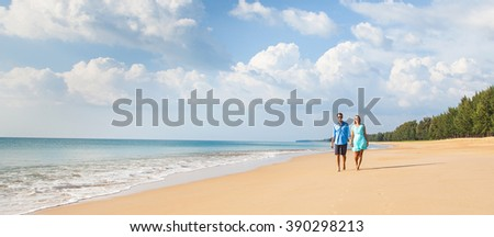 Couple walking on beach. Young happy interracial couple walking on beach smiling holding around each other.  Banner - stock photo