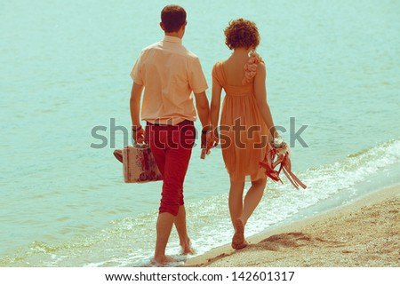 Couple walking on beach. Young happy married couple walking on beach holding around each other and holding their shoes. Sunny summer day. Outdoor shot - stock photo