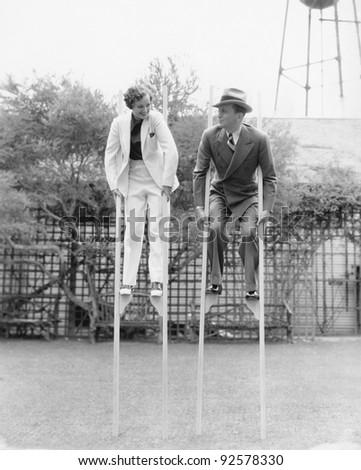 Couple walking on stilts - stock photo