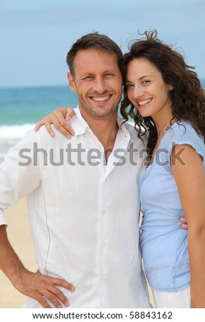 Couple walking on the beach - stock photo