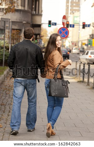 Couple walking on the street, Woman looking at camera. - stock photo