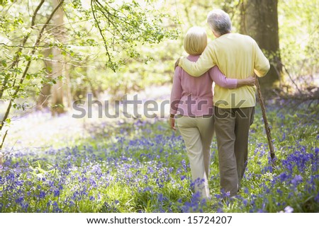 Couple walking outdoors with walking stick - stock photo