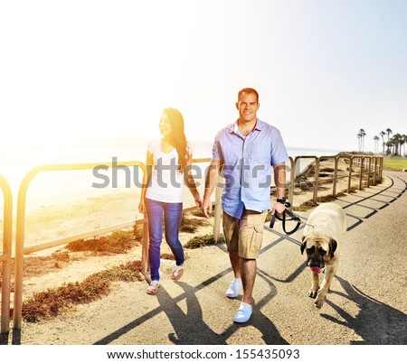 couple walking pet dog by the ocean - stock photo