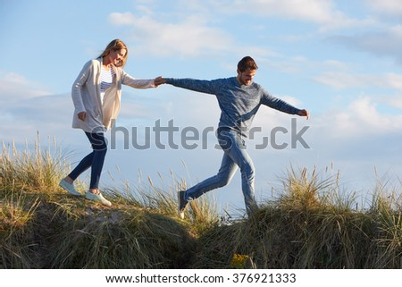 Couple Walking Through Sand Dunes Together - stock photo