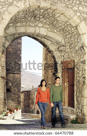 Couple walking through the gate of an italian village - stock photo
