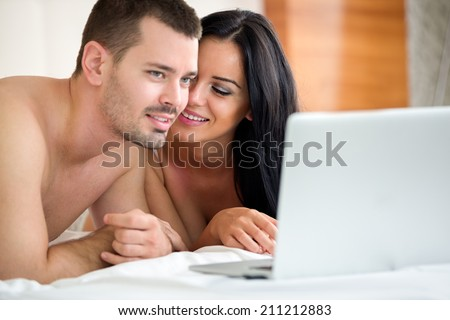 Couple watching porn movie over laptop in bedroom  - stock photo