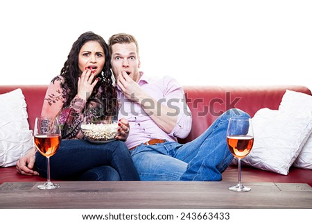Couple watching scary movie on the sofa with bowl of popcorn at home in the living room - stock photo