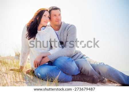 couple watching the sun fall down - stock photo