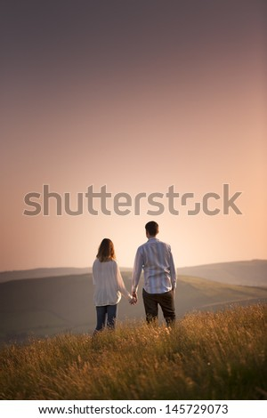 couple watching the sunset - stock photo