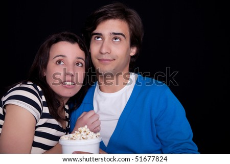 couple watching tv/cinema,  with popcorn, on black background. Studio shot - stock photo