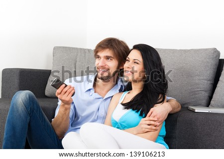 Couple watching tv in their living room at home, young happy smile man and woman sitting on couch, sofa, hold remote control - stock photo