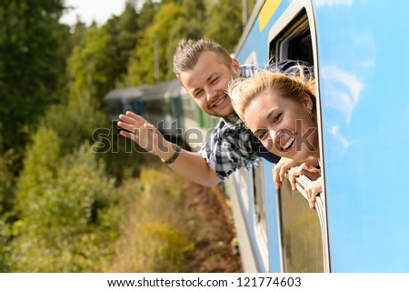Couple waving with heads out train window enthusiastic carefree happy - stock photo