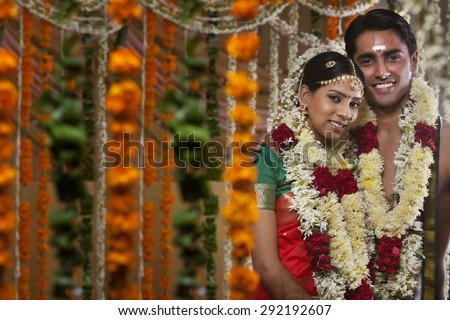 Couple wearing garlands standing together on their wedding day - stock photo