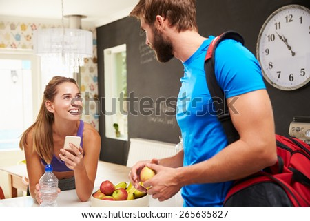 Couple Wearing Gym Clothing Talking In Kitchen - stock photo