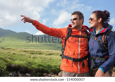 Couple wearing rain jackets and sunglasses admiring the scenery with man pointing in the countryside - stock photo