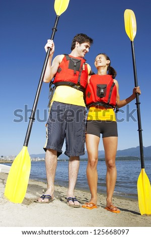 couple wearing red life jackets, standing on the beach side by side holding kayak paddle, looking at each other, blue sky and mountains seen at the back - stock photo