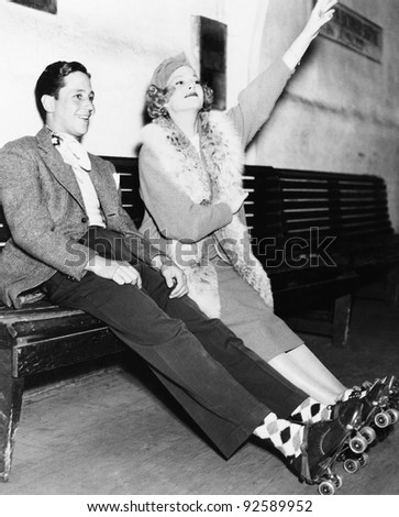 Couple wearing roller skates and sitting on a bench - stock photo