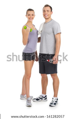 Couple wearing track suits smiling at camera. Staying isolated on white  - stock photo