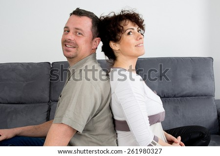 Couple who have fallen out over a disagreement sitting on a sofa - stock photo