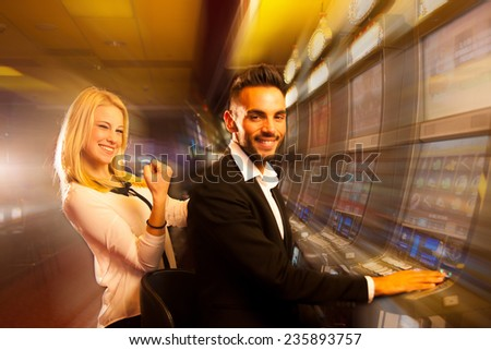 couple winning on slot machine in casino - stock photo