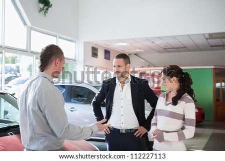 Couple with a car dealer in a car shop - stock photo