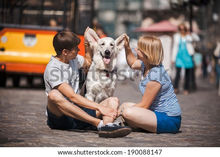 Couple with a dog on a ground - stock photo