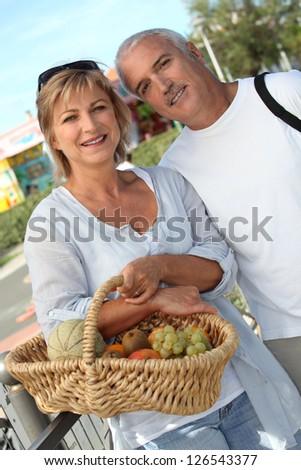 Couple with basket of fruit - stock photo