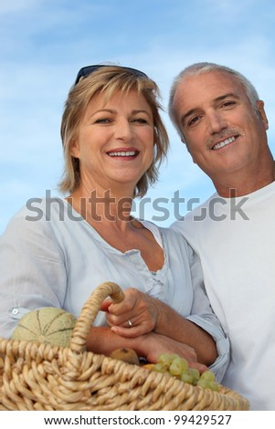 Couple with basket of fruits - stock photo