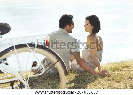 Couple with bicycle resting in front of the lake - stock photo