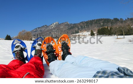 couple with blue and orange snowshoes in winter - stock photo