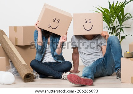 Couple With Cardboard Boxes On Their Heads With Smiley Face Sitting On Floor After The Moving House - stock photo