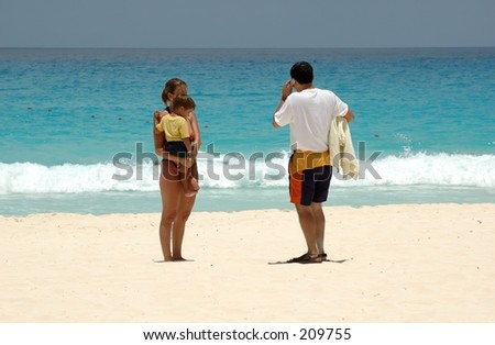 Couple with child in arms at the beach. - stock photo