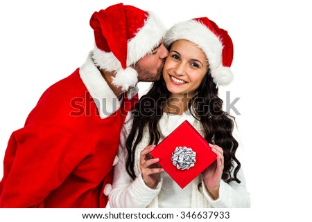 Couple with christmas hats holding red gift box on white screen - stock photo