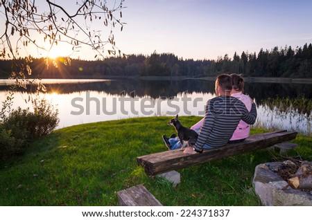 Couple with dog enjoy the late summer sunset - stock photo