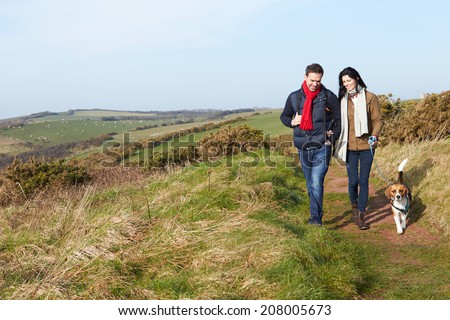 Couple With Dog Walking Along Coastal Path - stock photo