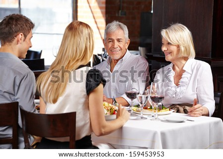 Couple with family eating out in a restaurant and talking - stock photo