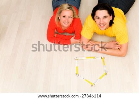 Couple with folding ruler shaped like house - stock photo