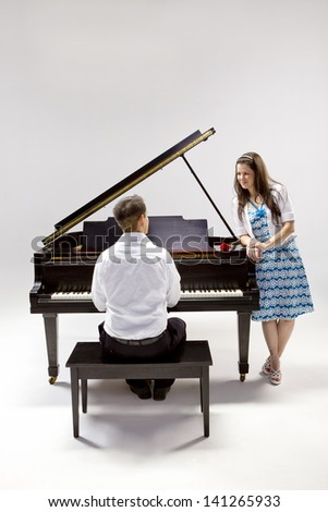 Couple with Grand piano 2 in white shirt, black pants and sundress with red rose. - stock photo