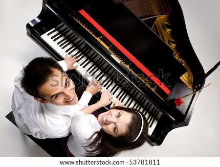 Couple with Grand piano 6 sitting at piano bench with red rose. - stock photo
