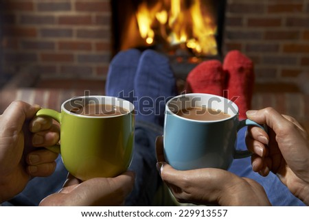 Couple With Hot Drink Relaxing By Fire - stock photo