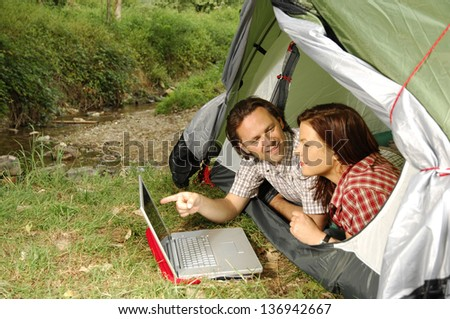 Couple with laptop lying in a tent, man pointing towards screen - camping serie - stock photo