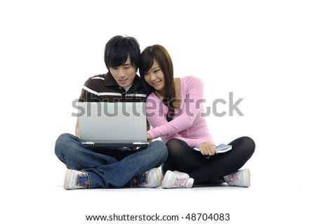 Couple with laptop, sitting on floor - stock photo